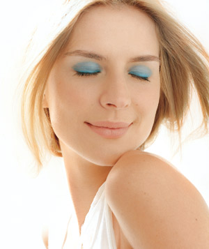 Model smiling wearing bright blue eye shadow