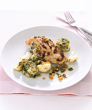 Zesty pesto sauce is spread on the chicken and baked in, then tossed with new potatoes on the side.