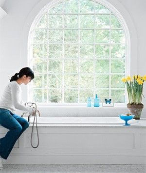 Woman cleaning the bathtub