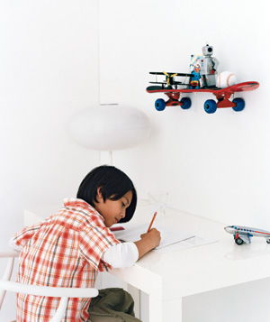 Boy writing at a desk with a skateboard as a shelf