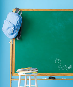Chalkboard, backpack, and a stool with books