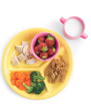 Kid's divided yellow plate with strawberries, chicken, pasta, broccoli, carrots and a glass of milk