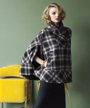 Model wearing a plaid wool cape