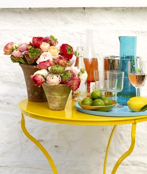 Terra cotta ranunculus flower arrangement on a yellow table