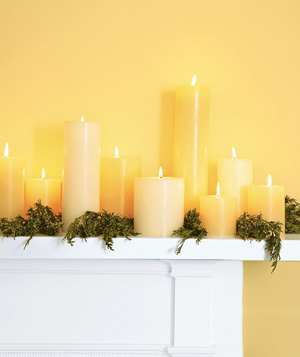 Lit candles in a yellow room on a white mantel