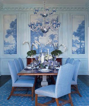 Dining room with blue carpet, walls, high-backed chairs and blue-accented chandelier
