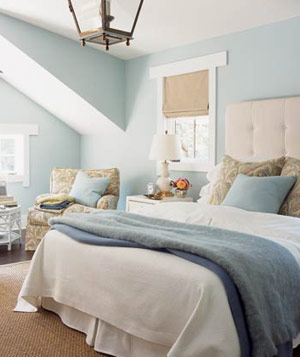Bedroom with blue walls accented with blue throw pillows and blanket