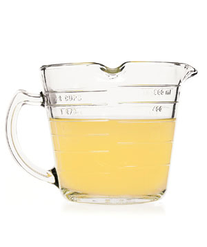Chicken broth in glass measuring cup