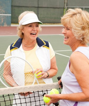 Women talking on a tennis court