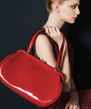 Model holding bright red patent leather handbag