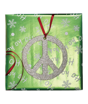 Gift wrapped in green holiday paper with silver peace sign