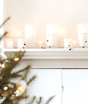 A mantel with tealights in frosted-glass vases