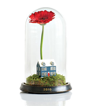 A round glass case with a red Gerbera daisy and a small house figurine