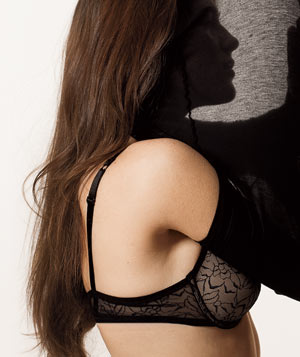 Profile of woman putting on a shirt with a bra on.