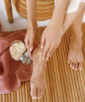 Woman applying a foot scrub