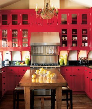 Kitchen with red cabinets and drawers, brass chandelier