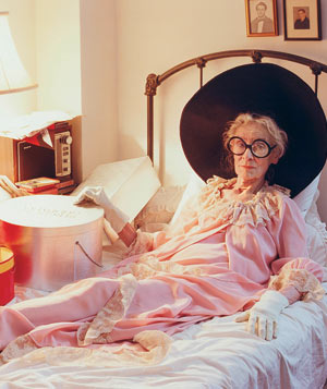Portrait of Mimi Weddell in bed with her hat collection