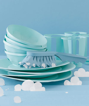 Paper construction of piled up dishes with scrubber in sink by Matthew Sporzynski