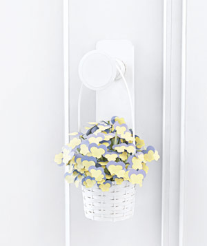 Paper construction of flowers in basket on doorknob by Matthew Sporzynski