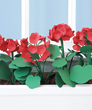 Paper construction of red flowers in a window box by Matthew Sporzynski