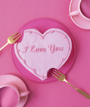 Paper construction of a heart-shaped cake with forks by Matthew Sporzynski