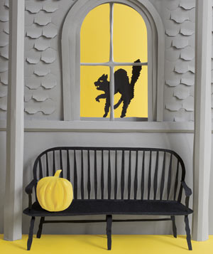 Paper construction of a black cat and pumpkin on bench by Matthew Sporzynski