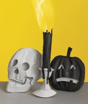 Paper construction of a skull, candle, and pumpkin by Matthew Sporzynski