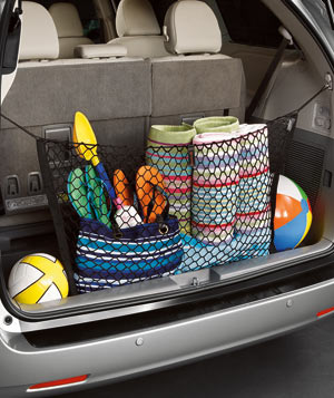 Toyota Sienna Minivan hatchback with a net filled with toys and supplies for the beach
