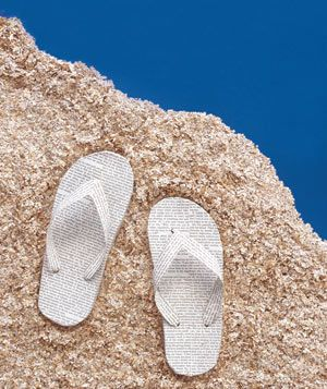 Paper construction of flip flops in sand by Matthew Sporzynski