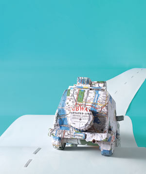 Paper construction of a car on road by Matthew Sporzynski