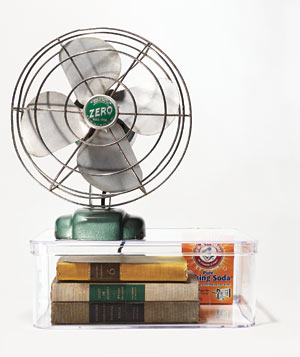 Fan on top of a container with musty vintage books and baking soda