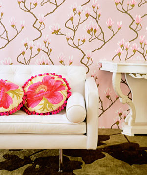 Modern pink floral wallpapered living room with a white sofa and graphic pillows