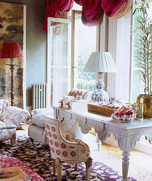A traditional sitting room with ornate painted table, floral upholstered gilt chair, pattern rug
