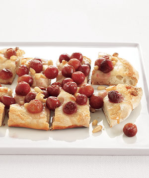 Use frozen pizza dough as a base for honey-drizzled grapes and pine nuts.