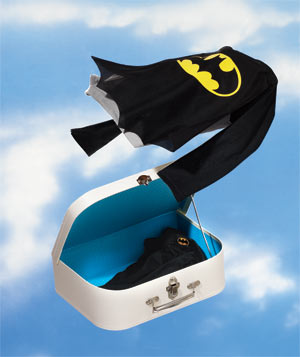 Batman costume flying in the sky with a white suitcase