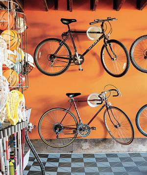Bikes hanging on an orange wall in a sports garage