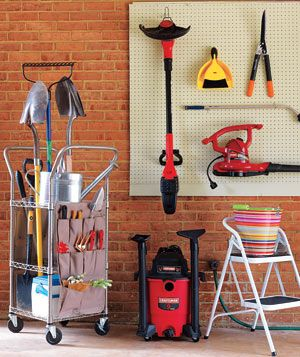 Pegboard holding tools with gardening equipment on a rolling organizer in a garage