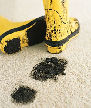 Muddy, yellow boots on carpet