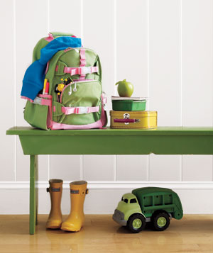 Kids' backpack and school supplies on a bench
