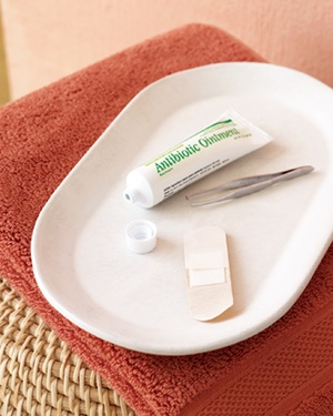 Antibiotic ointment, a band-aid and tweezers