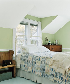 Green bedroom with a bench