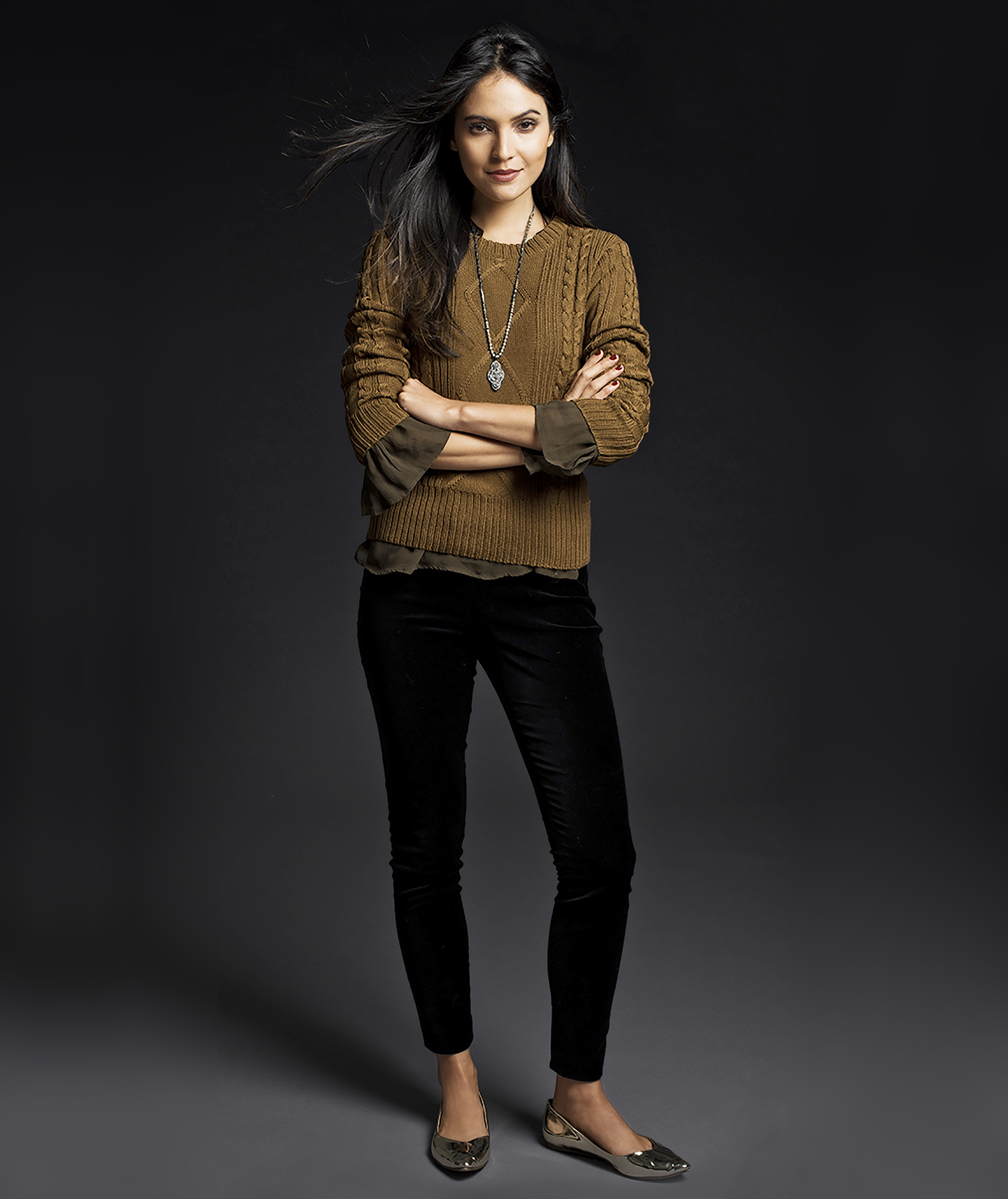 Model wearing brown sweater and black pants