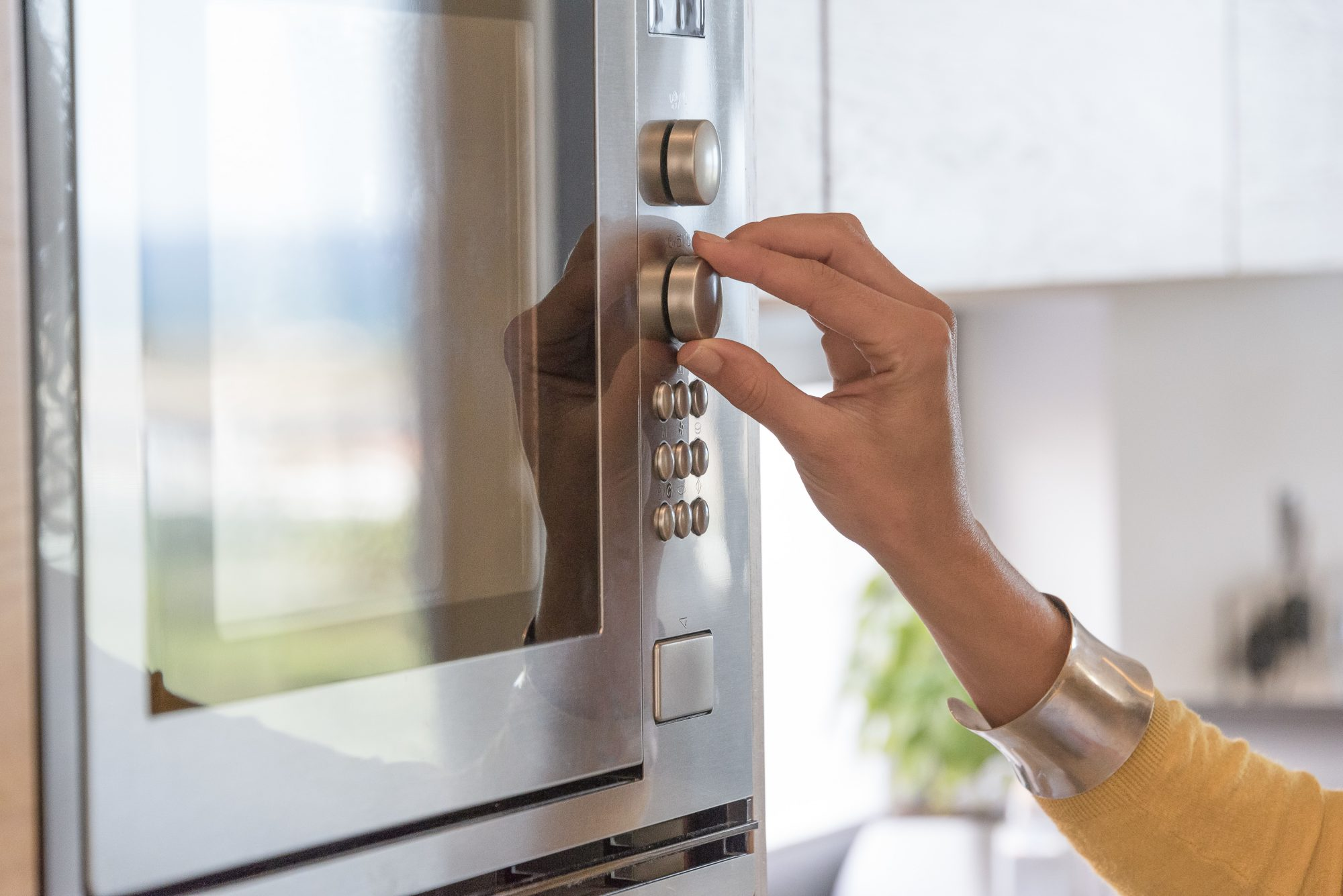 Woman Pressing Buttons on Microwave