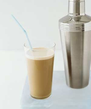 a glass of iced coffee and a cocktail shaker