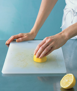 Woman cleaning a cutting board with lemon