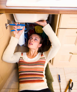 Woman fixing sink