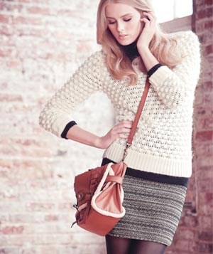 Model wearing white knit sweater, black turtle neck, grey patterned skirt and pvc messneger bag with faux fur