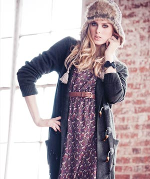 Model wearing wool and faux-fur hat, long grey cardigan and purple print dress