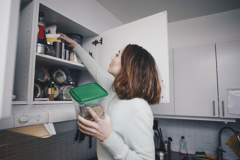 A Woman Getting Supplies From a Cabinet