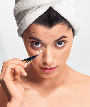 Model applying under-eye concealer